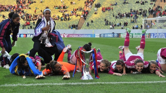 Olympique Lyonnais players celebrate with the trophy