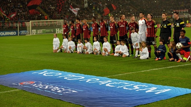 "AC Milan players behind a banner reading ""No to Racism - Respect"""