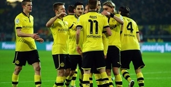 Marco Reus is mobbed by Dortmund team-mates after opening the scoring against Frankfurt