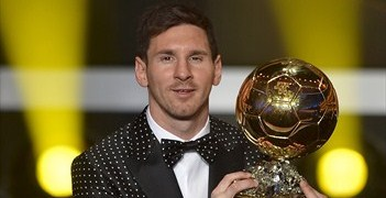 Lionel Messi poses with his award